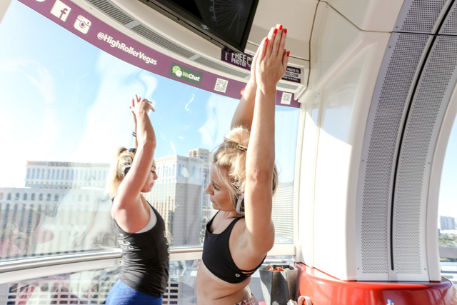Chelsea Pierce, right, volunteer, participates in a yoga session led by Silent Savasana instructor Markie Henderson, left, in a silent yoga set on the High Roller in Las Vegas, Wednesday, June 15, ...
