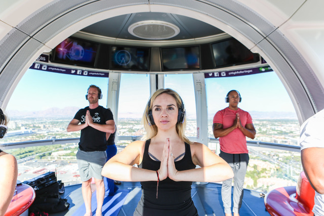 Diana Filipescu, center, volunteer, participates in a yoga session led by a Silent Savasana instructor in a silent yoga set on the High Roller in Las Vegas, Wednesday, June 15, 2016. (Elizabeth Br ...