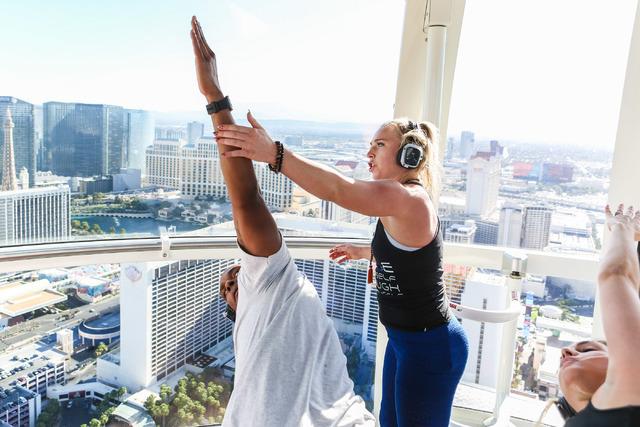 Silent Savasana instructor, Markie Henderson, aids volunteer Floyd Hanes during a silent yoga set on the High Roller in Las Vegas, Wednesday, June 15, 2016. (Elizabeth Brumley//Las Vegas Review-Jo ...