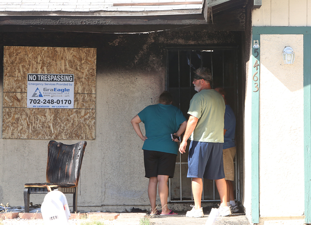 Neighbors survey the damage caused by a house fire at 5463 Yvonne Circle on Monday, June 13, 2016. One person was hospitalized and Two adults were treated for smoke inhalation. Bizuayehu Tesfaye/L ...