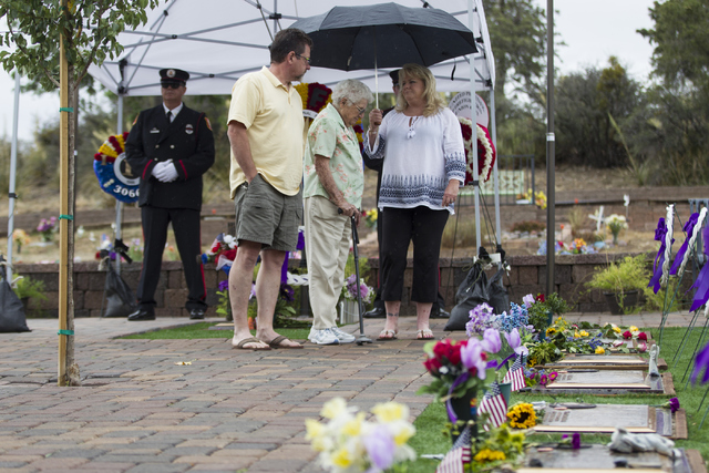 Erik Cahn, Joan Bigley and his wife Joni, pay their respects at the grave site for the 19 members of the Granite Mountain Hotshot crew killed while battling a fire in Yarnell, Ariz. three years ag ...