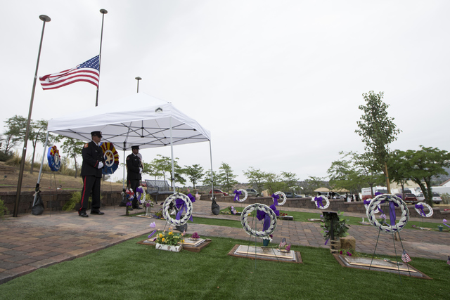 Honor guard members Chris Ketterer, left, with the Phoenix Fire Department, and Rick Olson, with the Central Arizona Fire Department, stand watch at the grave site for the 19 members of the Granit ...