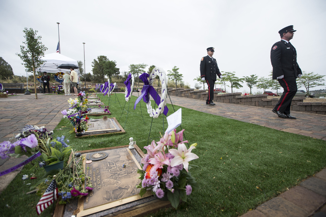 Honor guard members Chris Ketterer, left, with the Phoenix Fire Department, and Rick Olson, with the Central Arizona Fire Department, leave their post on the grave site for the 19 members of the G ...