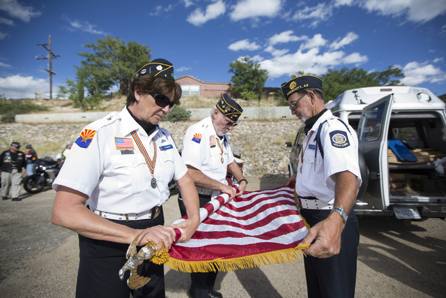 Members of the American Legion Post 6 Honor Guard from left, Jan Bowles, Capt. Dan Tillmans, and Mike Shafer, fold an American flag after attending the Third Anniversary Memorial Service of the Ya ...