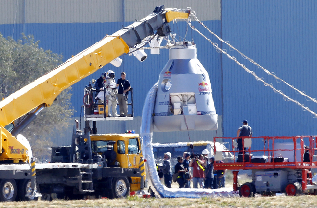 Felix Baumgartner, in pressurized suit on platform at left, prepares to enter the balloon capsule in Roswell, N.M., in 2012. (The Associated Press)