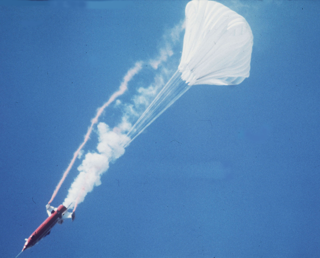 A parachute opens behind the rocket-powered Sky Cycle X-2, containing American motorcycle stuntman Evel Knievel, as he attempts to jump the Snake River Canyon, Idaho, in 1974.  (The Associated Press)