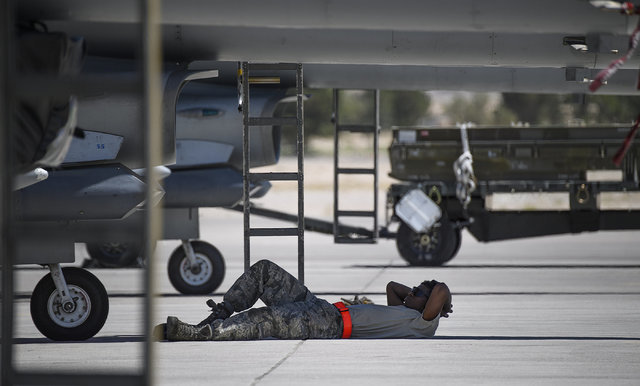 In temperatures approach 100 degrees, Airman 1st Class Darius Moss from Shaw Air Force Base's 79th Fighter Squadron, finds a sliver of shade from a F-16 Fighting Falcon during Red Flag at Nellis A ...