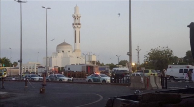 General view of security personnel in front of a mosque as police stage a second controlled explosion, after a suicide bomber was killed and two other people wounded in a blast near the U.S. consu ...