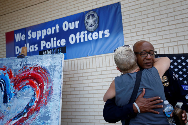 A woman hugs a police officer at a makeshift memorial at police headquarters following the multiple police shootings in Dallas, July 12, 2016.  (Carlo Allegri/Reuters)