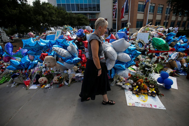 A woman walks past a makeshift memorial at police headquarters following the multiple police shootings in Dallas, July 12, 2016.  (Carlo Allegri/Reuters)