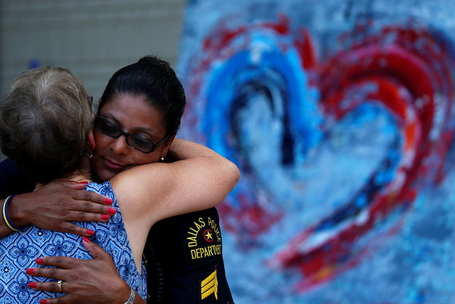 A woman hugs a Dallas police officer at a makeshift memorial at police headquarters following the multiple police shootings in Dallas, July 12 2016.  (Carlo Allegri/Reuters)