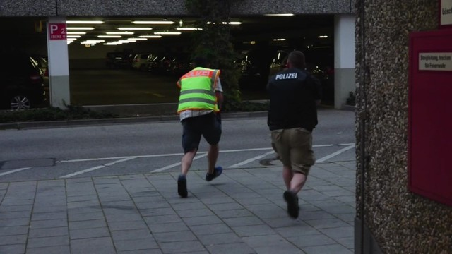 A screen grab taken from video footage shows plain clothes police officers running towards car park of the Olympia shopping mall during shooting rampage in Munich, July 22, 2016.  dedinac/Marc Mue ...