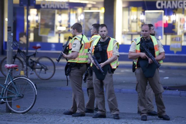 Police officers stand guard outside the main train station following a shooting rampage at the Olympia shopping mall in Munich, July 22, 2016. (Michael Dalder/Reuters)