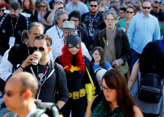 Gina Gianni of Chicago comes dressed as an animated Batgirl as she waits in a crowd to cross the street  to attend the pop culture event Comic-Con International in San Diego, California, United St ...