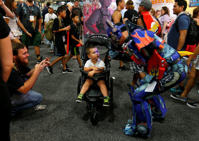 A young boy looks unimpressed as his father asks to take a picture with an attendee dressed as a Transformer at the pop culture event Comic-Con International in San Diego, California, United State ...