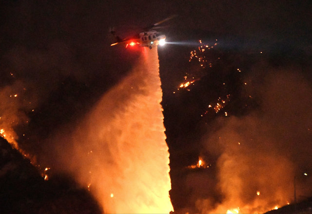 A Los Angeles County Fire Department helicopter makes a water drop at night during the so-called Sand Fire in the Angeles National Forest near Los Angeles, California, U.S. July 24, 2016. REUTERS/ ...