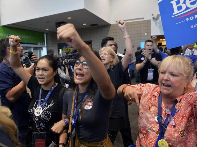 Supporters of former Democratic Presidential candidate Senator Bernie Sanders walk out in protest after he moved to suspend the rules and nominate Hillary Clinton during the Democratic National Co ...