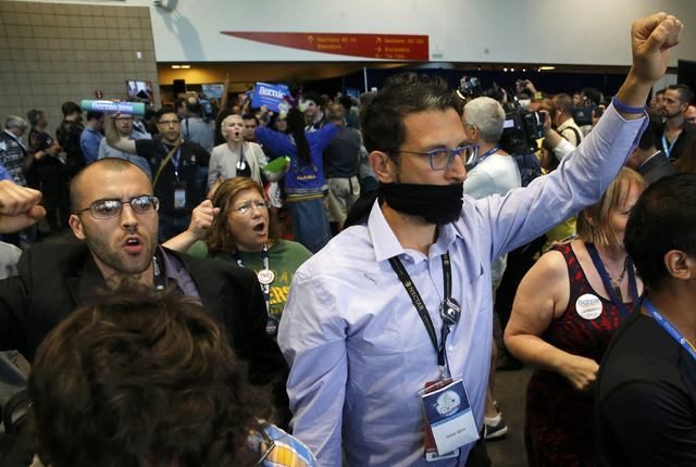Supporters and delegates of former Democratic presidential candidate Senator Bernie Sanders walk out after Hillary Clinton was nominated during the second day at the Democratic National Convention ...