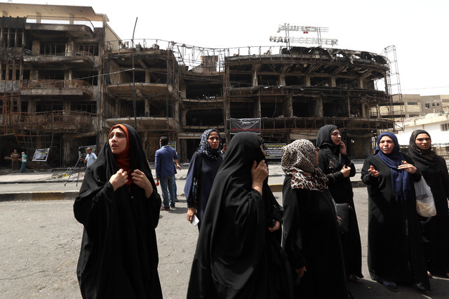 Iraqi women wait for their family members who are missing after a car bomb went off in a commercial area in Karada neighborhood, Baghdad, Iraq, Monday, July 4, 2016. (AP Photo/Hadi Mizban)