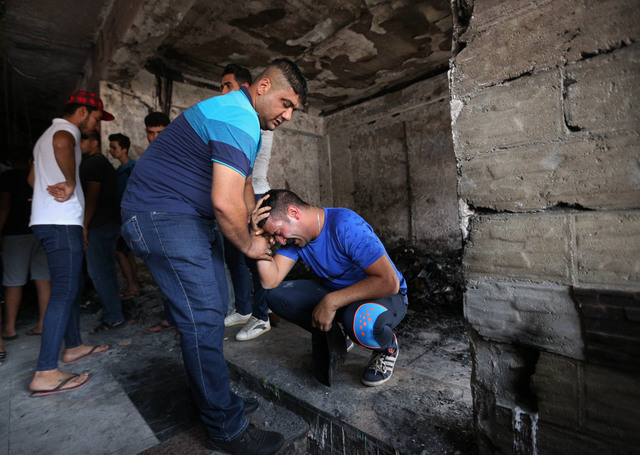 Iraqi men grieve at the scene of a deadly suicide car bomb at a commercial area in Karada neighborhood, Baghdad, Iraq, Monday, July 4, 2016. More than 100 people died Sunday in a car bombing that  ...