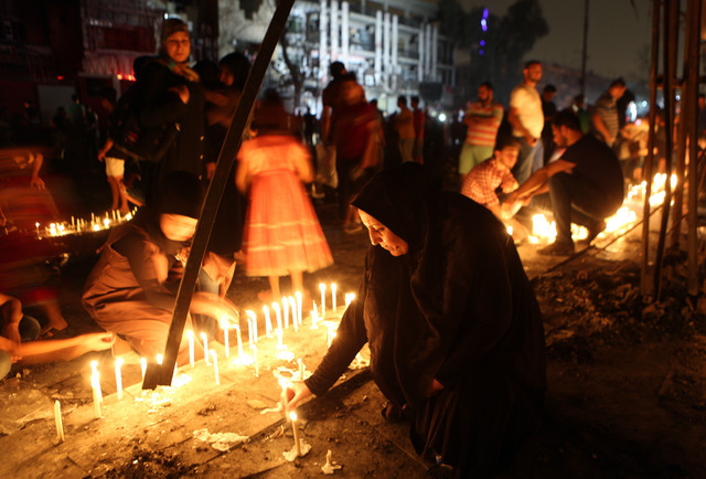 People light candles at the scene of a massive car bomb attack in Karada, a busy shopping district where people were shopping for the upcoming Eid al-Fitr holiday, in the center of Baghdad, Iraq,  ...