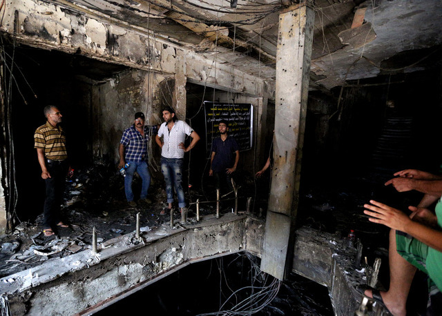 Iraqi men look for victims who went missing after a car bomb hit Karada, a busy shopping district in the center of Baghdad, Iraq, Monday, July 4, 2016. More than 100 people died Sunday in a car bo ...