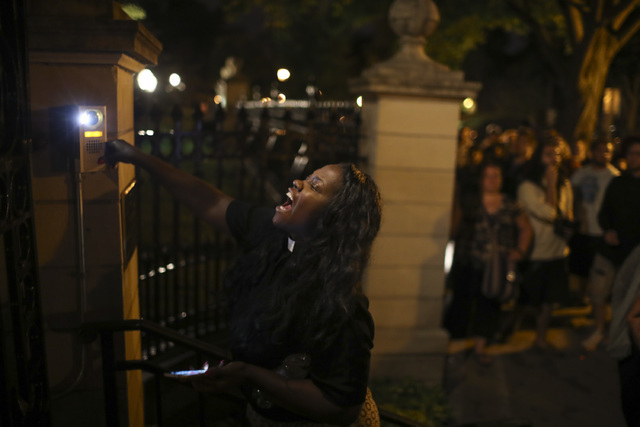 A woman rings the doorbell at the gate of the Governors Mansion as demonstrators gather in St. Paul, Minn., protesting a police-involved shooting early Thursday, July 7, 2016. (Jeff Wheeler/Star T ...