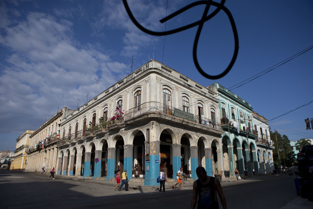 A loose cable dangles from above as people walk past colonial buildings in Havana, March 19, 2016. Scheduled commercial airline service to Havana from 10 American cities won tentative government a ...