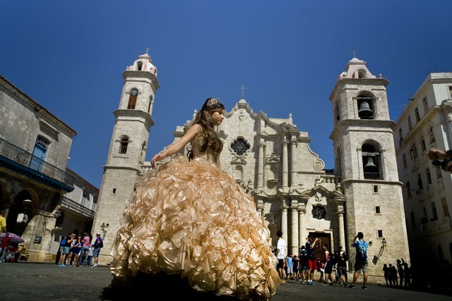 """A """"quinceanera"""" poses in front of the cathedral as tourists line up to enter the building, in Havana, March 14, 2016. Scheduled commercial airline service to Havana from 10 American cities won ten ..."""