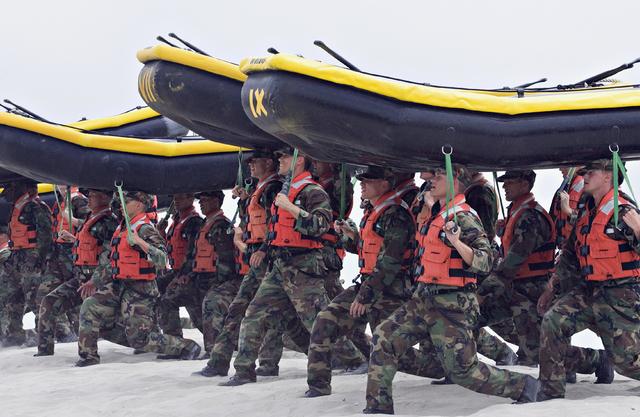 Navy SEAL trainees carry inflatable boats at the Naval Amphibious Base Coronado in Coronado, Calif., May 14, 2009. (Denis Poroy/AP)