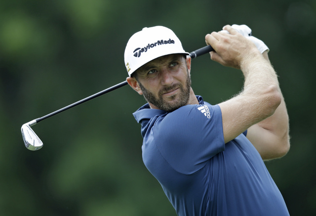 In this July 1, 2016, file photo, Dustin Johnson tees off on the third hole during the second round of the Bridgestone Invitational golf tournament at Firestone Country Club in Akron, Ohio. The Br ...