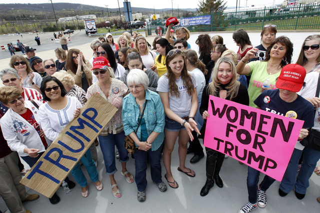 In this photo taken April 25, 2015, a group of women hold signs and shout their support as they wait on line to attend a rally for Republican presidential candidate Donald Trump in Wilkes-Barre, P ...