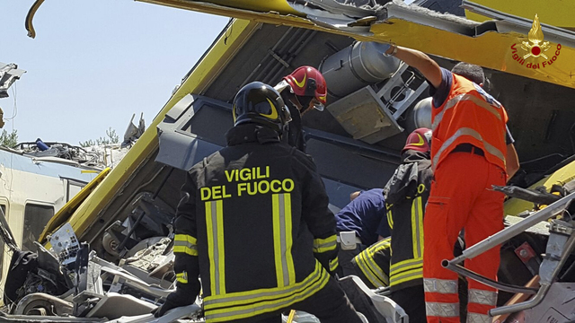 Italian firefighters Vigili del Fuoco inspect the wreckage of two commuter trains after their head-on collision in the southern region of Puglia, killing several people, Tuesday, July 12, 2016.  ( ...