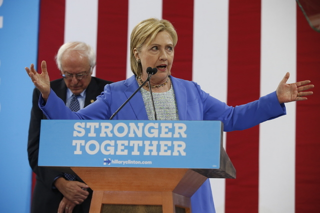 Sen. Bernie Sanders, I-Vt., listens as Democratic presidential candidate Hillary Clinton speaks during a rally in Portsmouth, N.H., Tuesday, July 12, 2016, where Sanders endorsed Clinton for presi ...