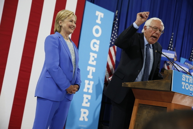 Democratic presidential candidate Hillary Clinton listens as Sen.Bernie Sanders, I-Vt., speaks during a rally in Portsmouth, N.H., Tuesday, July 12, 2016, where Sanders endorsed Clinton. (Andrew H ...
