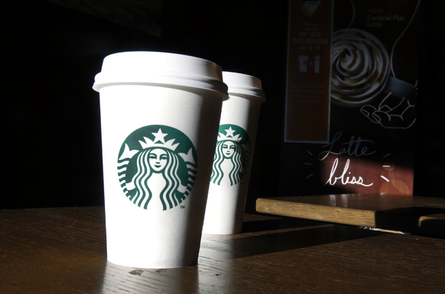 In this Friday, Jan. 17, 2014, Starbucks cups are shown mugs in a cafe in North Andover, Mass. (AP Photo/Elise Amendola, File)