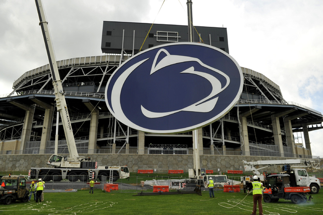In this May 15, 2014 file photo, a logo is lifted by crane to the back of a scoreboard at Penn State's Beaver Stadium in State College, Pa.   Judge Gary Glazer is expected to release records Tuesd ...