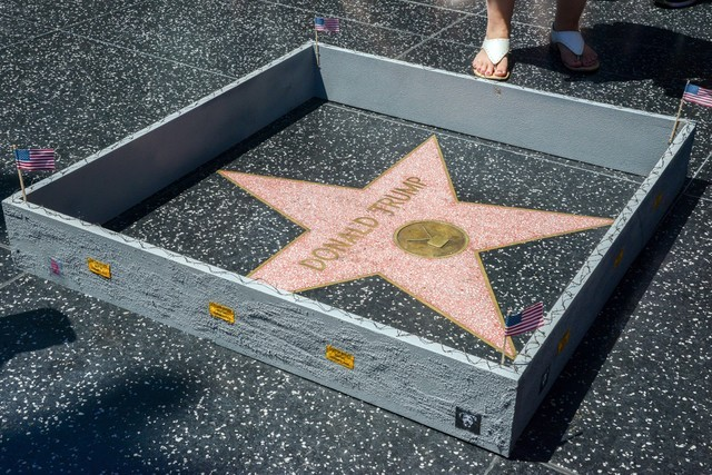 """A six-inch high, concrete-appearing """"wall,"""" created by an artist known as Plastic Jesus, surrounds the Hollywood Walk of Fame star of Donald Trump in Los Angeles, Tuesday, July 19, 2016. The tiny  ..."""