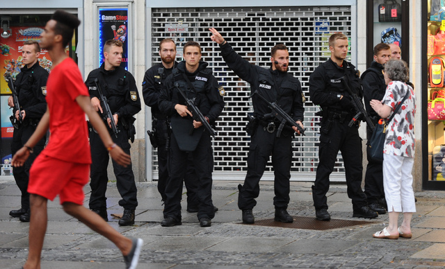 Police officers securing the Stachus hotel talk to residents after a shooting was reported there in Munich, southern Germany, Friday, July 22, 2016. Several people have been reported to be killed. ...