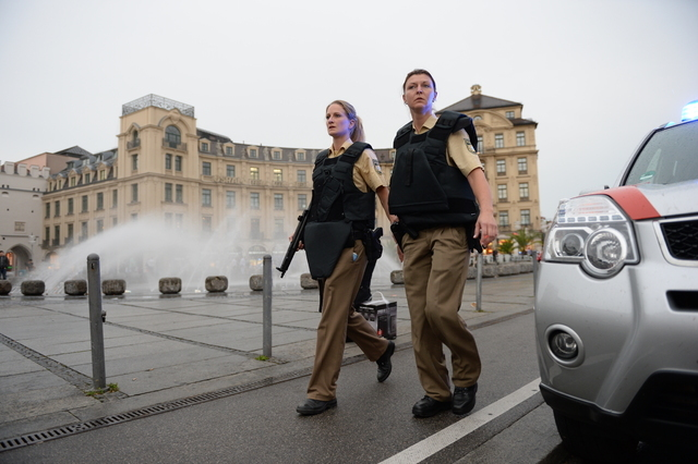 Police officers in protective gear woperate at Karlsplatz (Stachus) square after a shooting in the Olympia shopping centre was reported in Munich, southern Germany, Friday, July 22, 2016. (Andreas ...
