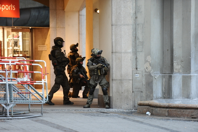 Heavily armed police forces operate at Karlsplatz (Stachus) square after a shooting in the Olympia shopping centre was reported in Munich, Friday, July 22, 2016. (Andreas Gebert/dpa via AP)