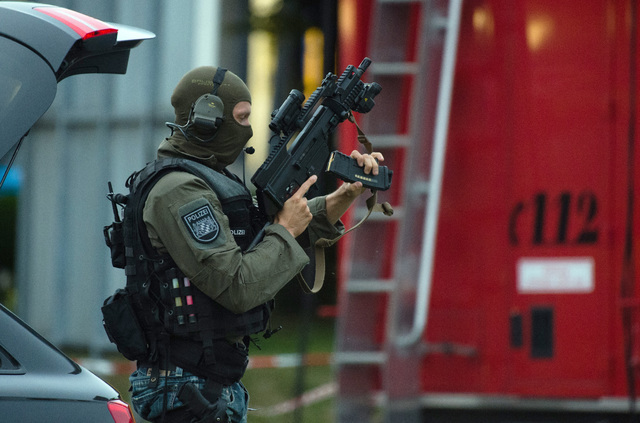 Police officer search a residential area near the Olympia shopping centre after a shooting was reported there in Munich, southern Germany, Friday, July 22, 2016. Several people have been reported  ...