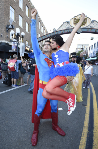 Sergio Valente, dressed as Superman, lifts Jessica Randall, dressed as Vixen, as she gives him a kiss outside of the convention center on day one of Comic-Con International held at the San Diego C ...