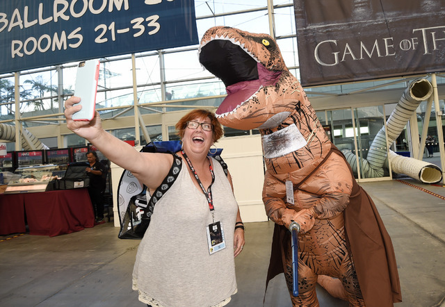 """Inger Utke, left, takes a selfie with Edwin Galarza, dressed as a """"Star Wars"""" themed dinosaur, during Preview Night at Comic-Con International held at the San Diego Convention Center, Wednesday, J ..."""