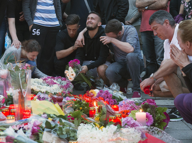People mourn behind flower tributes near the Olympia shopping center where a shooting took place leaving nine people dead the day before, in Munich, Germany, Saturday, July 23, 2016. (Jens Meyer/A ...