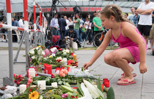 A girl puts down flowers in front of the Olympia shopping center were a shooting took place leaving nine people dead the day before on Saturday, July 23, 2016 in Munich, Germany. (Sebastian Widman ...
