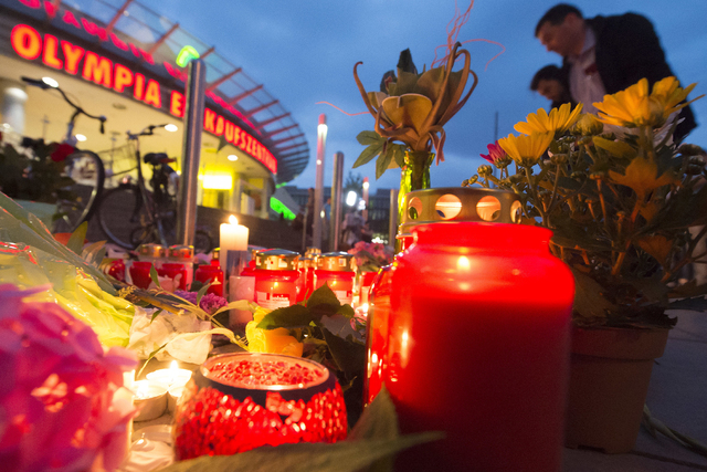 People gather to read tributes among the flowers and candles near to the Olympia shopping center where a shooting took place leaving nine people dead the day before in Munich, Germany, Saturday, J ...