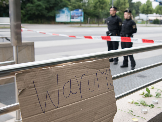"A sign reading ""why"" is fixed where a shooting took place in front of a fast food restaurant leaving nine people dead the day before on Saturday, July 23, 2016 in Munich, Germany. (Sebastian Widma ..."