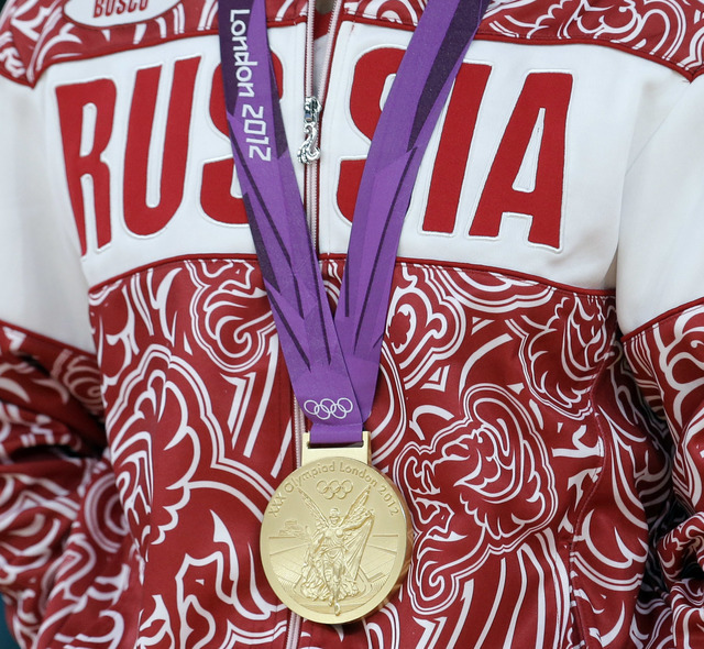 FILE - In this Aug. 10, 2012 file photo a gold medalist from Russia participates in a medals ceremony at the 2012 Summer Olympics in London. The IOC's ruling 15-member executive board will meet Su ...