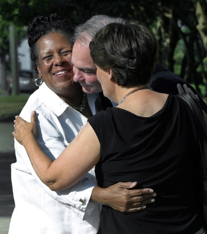 A fellow parishoner, left of St. Elizabeth's Catholic Church in Richmond, Va. greets Sen. Tim Kaine, center, and his wife, Anne Holton as they arrive for Mass St. Elizabeth Catholic Church, their  ...
